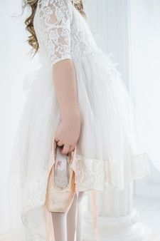 Little girl ballerina in a beautiful white dress holding pointe shoes