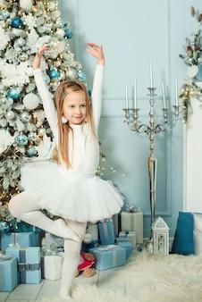 Little girl in ballerina costume dancing near christmas tree.