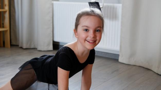 어린 소녀 발레리나 또는 체조 선수가 집에서 운동을 연습했습니다.