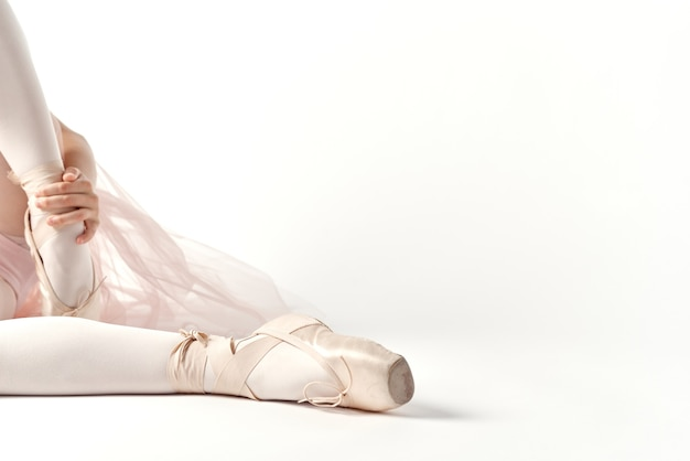 Little girl ballerina in a white suit with pointe shoes