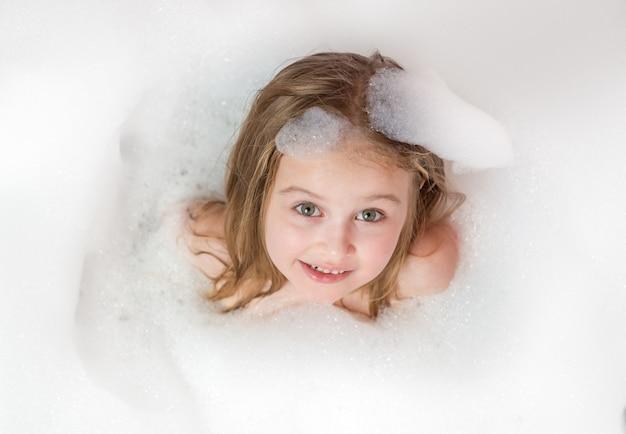 泡と泡のお風呂で小さな女の子を浴びる