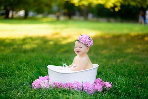 少女は公園の牛乳風呂で入浴します。女の子は夏を楽しんでいます。