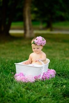Маленькая девочка купается в молочной ванне в парке