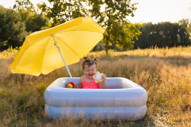 Маленькая девочка купается в надувном бассейне.