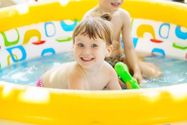 어린 소녀는 뜨거운 여름 날에 야외에서 노란색 풍선 수영장 얕은 수영장에서 목욕. 수영 풀에있는 아이들