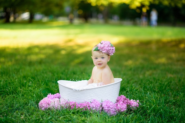 Little girl bathes in a milk bath in the park.