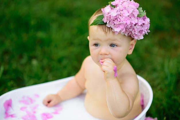 Little girl bathes in a milk bath in the park.