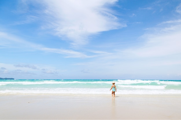 Little girl bathes in the sea on the beach with white sand