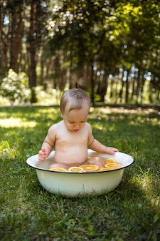 A little girl bathes in a white basin with oranges in nature