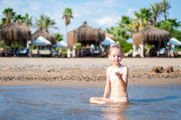 Little girl in a bathing suit playing on the beach by the sea
