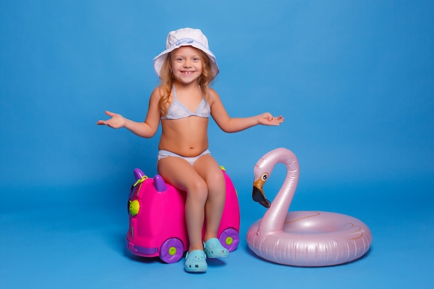 A little girl in a bathing suit sits on a suitcase on a blue background. travel concept
