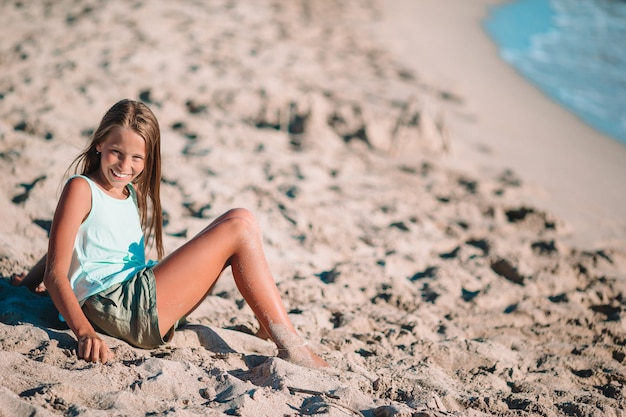 Little girl on the beach plays with sand at sunset