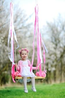 Little girl in a beautiful dress riding on a swing.