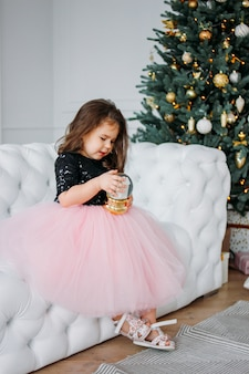 Little girl in beautiful dress tutu skirt with glass ball in living room on  of christmas tree