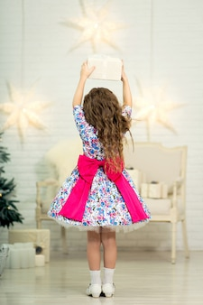 Little girl in a beautiful dress with a big bow holds a box with a gift over her head