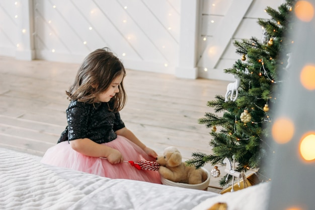 Little girl in beautiful dress with dog toy in bedroom