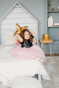 Little girl in beautiful dress with star pillow in bedroom