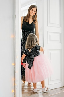 Little girl in beautiful pink dress with tutu skirt looks at the door with her mother