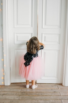 Little girl in beautiful pink dress with tutu skirt looks at door
