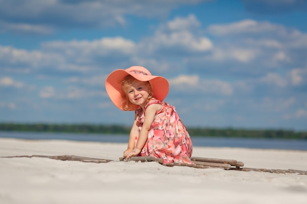 A little girl in a beautiful sarafna plays in the sand on the beach.