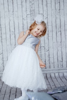 Little girl in beautiful white dress on a light wooden background. shine, silver, xmas