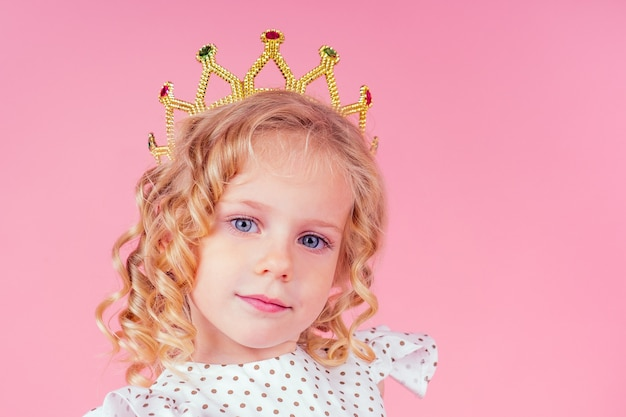 Маленькая девочка королева красоты голубые глаза, кудри светлая прическа с короной тиары на голове в милом белом. платье в горошек позирует в студии на розовом фоне. празднование дня рождения, конкурс красоты