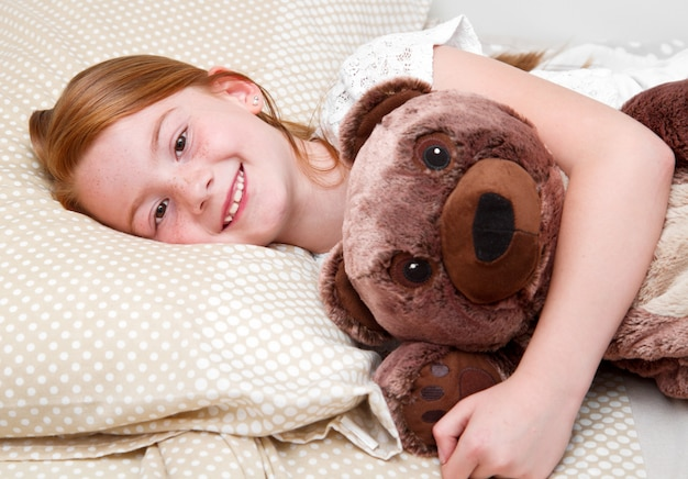 Little girl in bed hugging  the teddy bear