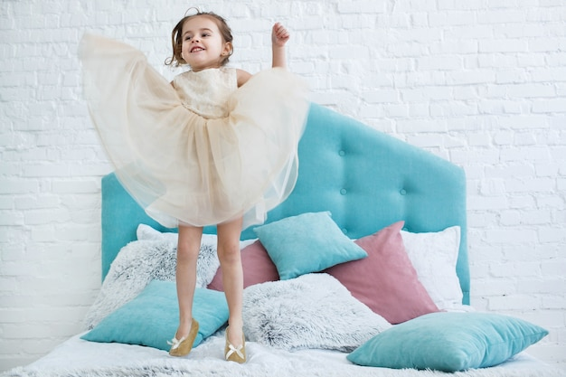 Little girl in beige dress jumps on bed with pink and blue pillows