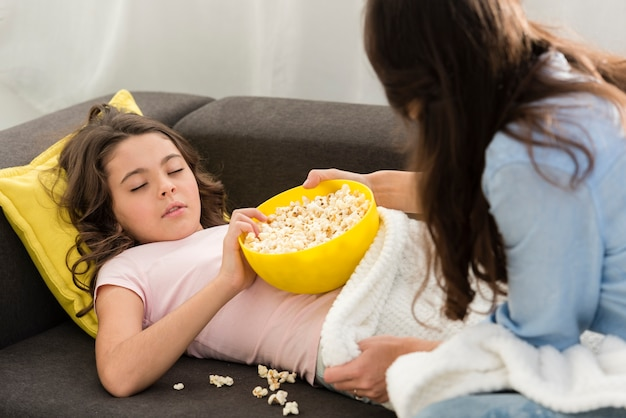 Little girl being sleepy with a bowl of popcorn