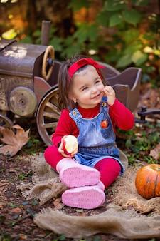 Маленькая девочка возле трактора с тыквами ест яблоко
