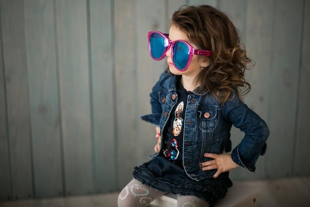 Bambina in grandi occhiali da sole