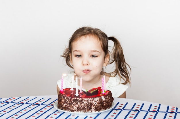 Little girl and birthday cake, blows out candles, makes a wish, cake and candles, birthday gifts, family, mom and dad
