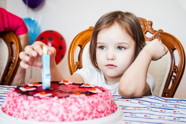 Little girl, birthday girl blowing out candles on cake, birthday celebration with friends