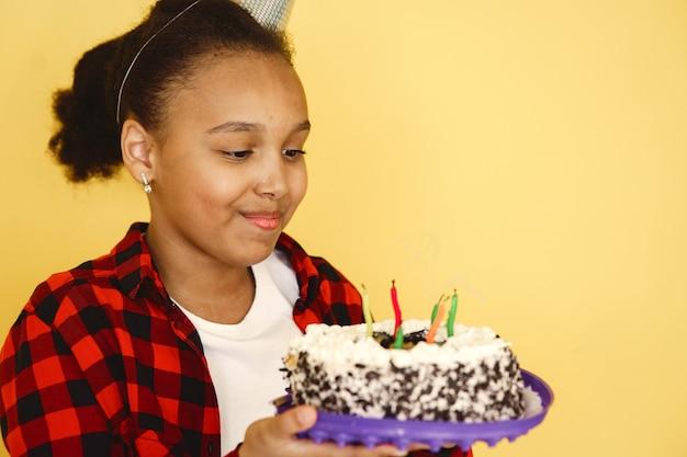 小さな女の子の誕生日は黄色の壁に分離されました。ケーキを持っている子供。