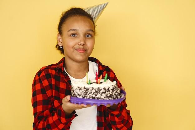 노란색 벽에 고립 된 어린 소녀 생일입니다. 아이 들고 케이크.
