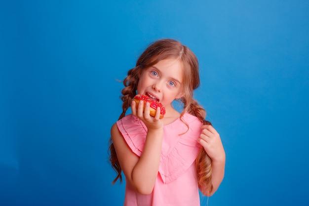 A little girl bites a donut