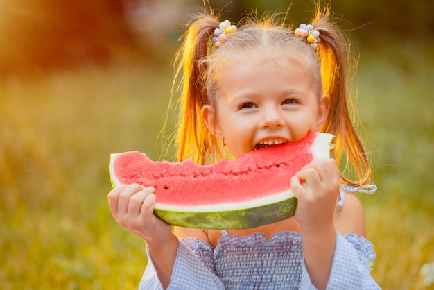 Little girl bites a slice of watermelon