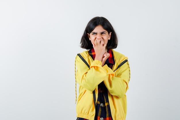 Bambina che si morde le unghie in camicia a quadri, giacca e sembra preoccupata