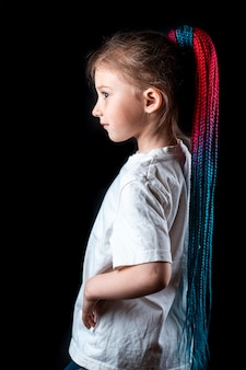 Little girl on a black background with turquoise and pink afro elastic bands, pigtails tied in a ponytail cool