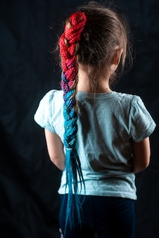 Little girl on a black background with turquoise and pink afro elastic bands, pigtails tied in a ponytail