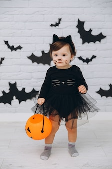 A little girl in a black cat costume with a pumpkin basket