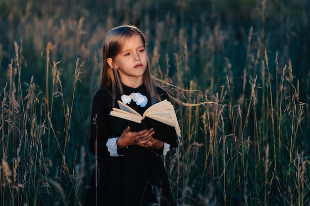 A little girl in a black dress stands in tall grass and holds a green book in the light of the setting sun. a child with a pensive facial expression.