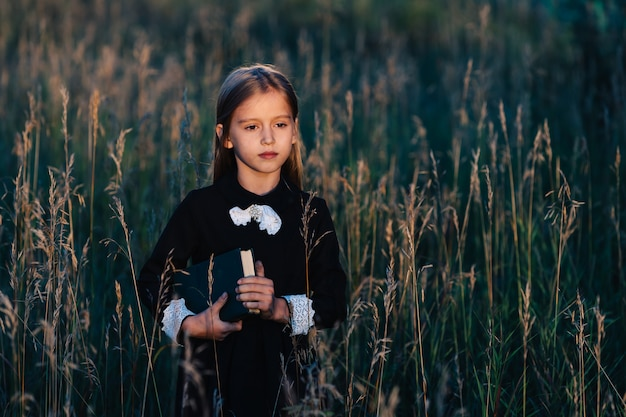 A little girl in a black dress stands in tall grass and holds a green book while looking at the sunset.