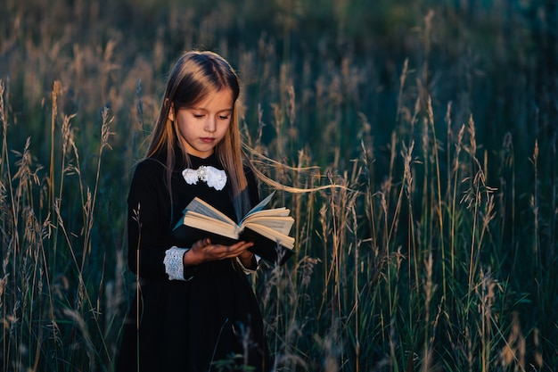 A little girl in a black dress stands in tall grass and reads a green book in the light of the setting sun.