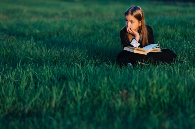 A little girl in black sits on the grass and holds a green book in the light of the setting sun. the child looks thoughtfully into the distance outdoors in nature.