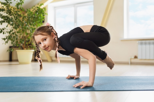 Little girl in black sportswear practicing yoga doing handstand exercise kakasanu or crow pose on a gymnastic mat in the studio