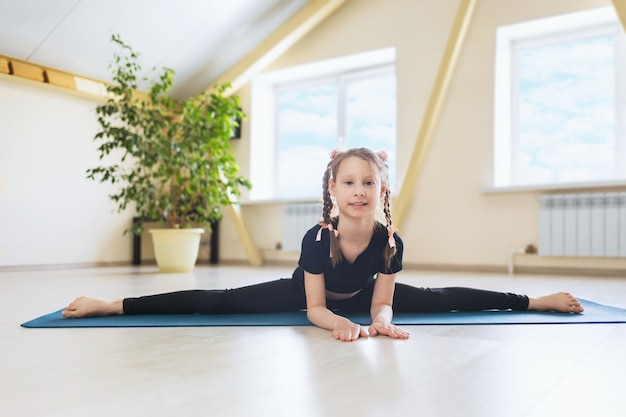 Little girl in black sportswear practicing yoga performs a transverse split on a gymnastic mat the samokanasana exercise