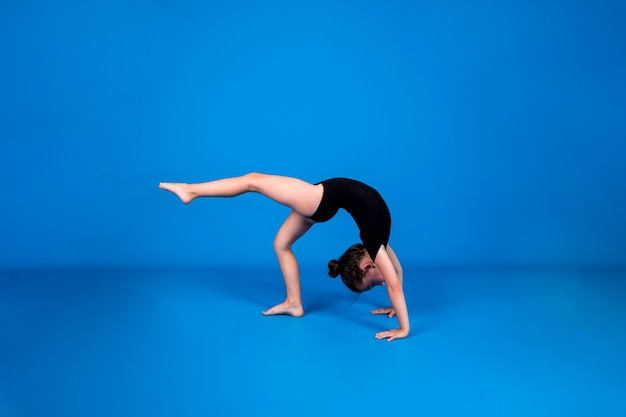 A little girl in a black swimsuit performs a rhythmic gymnastics exercise on a blue background with a place for text
