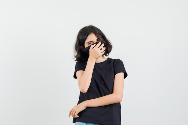 Bambina in maglietta nera, maschera tenendo la mano sulla bocca mentre ride, vista frontale.