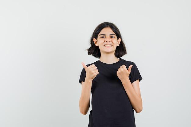 Bambina in maglietta nera che mostra i doppi pollici in su e che sembra felice, vista frontale.